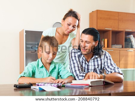 Teenager schoolboy and parents studying together