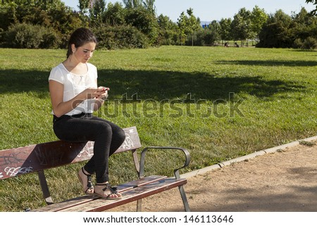 teenager sending a message via the phone in a park