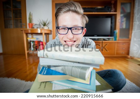 Teenager sitting in front of books  and smiling to the camera. - stock photo