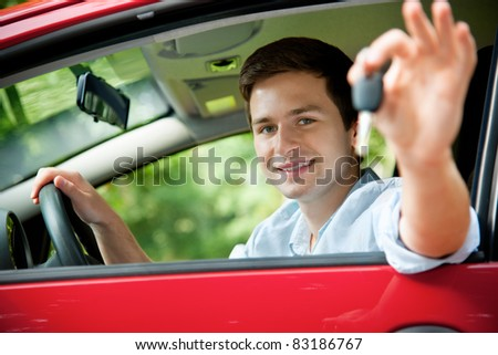 teenager sitting in new car and shows the keys - stock photo