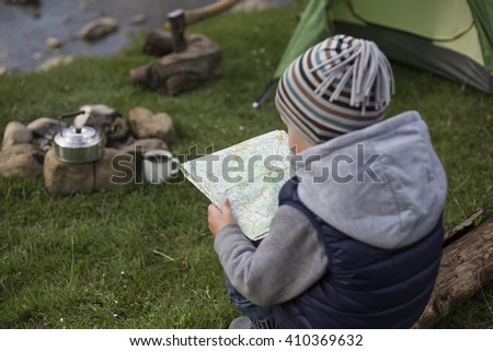 Teenager sitting near a fire in camping and looking at a map. - stock photo