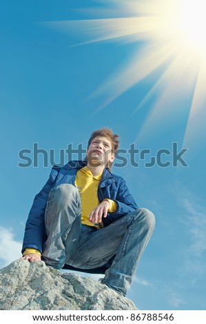 teenager sitting on a rock  and  looks in distance. - stock photo