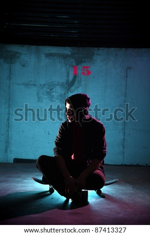 teenager sitting on a skateboard at night - stock photo