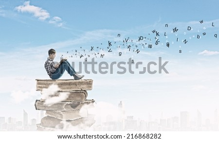 Teenager sitting on pile of books and reading - stock photo