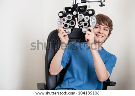Teenager smiling while holding phoropter at the clinic - stock photo