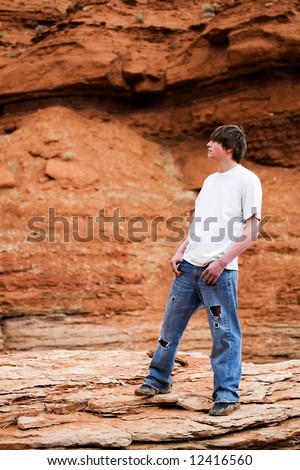 teenager standing on a rock in the mountains of wyoming. Muddy shoes, holes in jeans, hands in pocket.