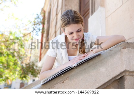 Teenager student girl reading her notebook while leaning on the banister of an old stone university college building during a sunny day, smiling.