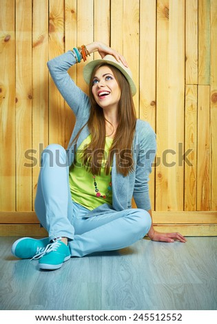 Teenager style young woman sitting on a floor. Looking up. Hat.