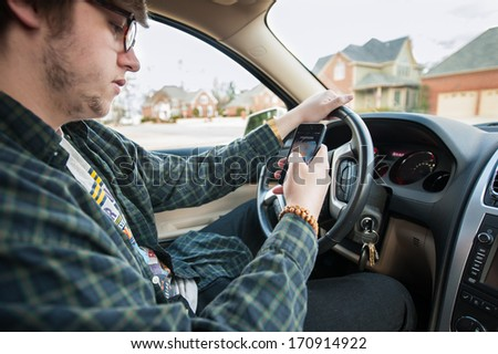 teenager texting and driving - stock photo