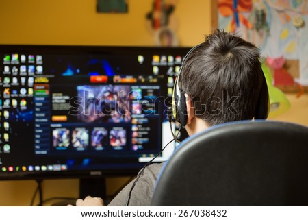 Teenager using computer at home with headphones, play game in his child room - stock photo