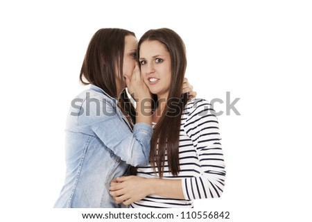 teenager whispering her sister in her ear on white background - stock photo