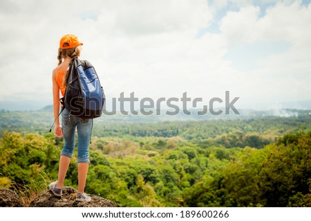 teenager with a backpack standing on a mountain top
