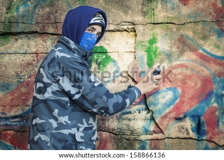 Teenager with color spray can near the wall