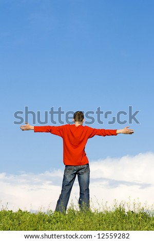 teenager with his arms wide open - stock photo