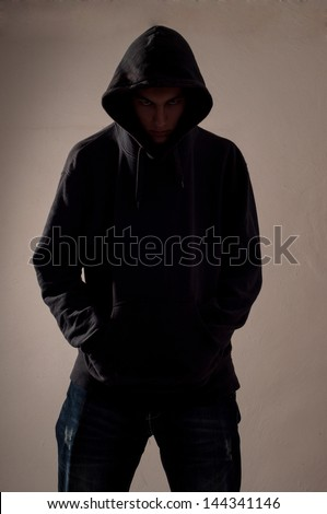 teenager with hoodie look ahead against a dirty gray wall - stock photo