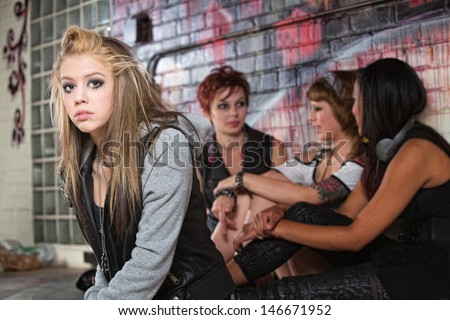 Teenager with low self-esteem near three friends - stock photo