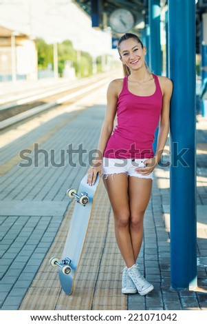 Teenager with skateboard portrait in train station.