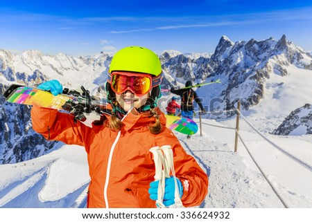 Teenager with ski in the blue sky ant mountains background - stock photo