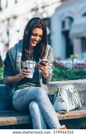Teenager with take-away coffee in the city, sitting on the bench, using smart phone.