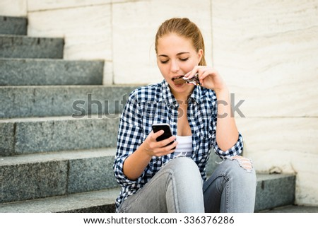 Teenager - young woman eating chocolate in street and looking in phone - stock photo