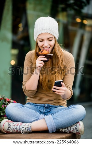 Teenager - young woman eating muffin in street and looking in phone - stock photo