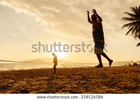 teenagers balance slackline on sunrise beach silhouette - stock photo