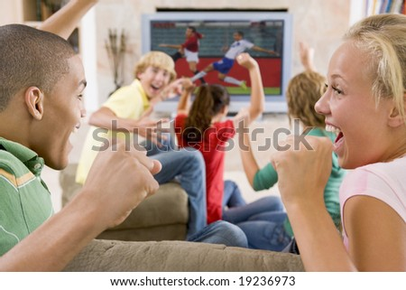 Teenagers Cheering At The TV - stock photo