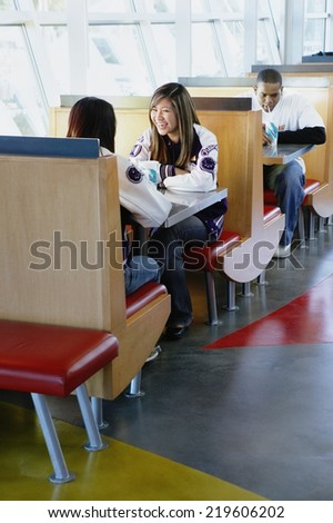 Teenagers eating in restaurant - stock photo
