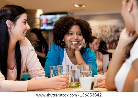 teenagers girls in cafe chatting in cafe, leisure activities - stock photo