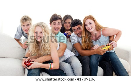 Teenagers having fun playing video games in the living-room - stock photo