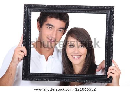 Teenagers holding photo frame - stock photo