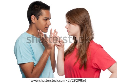 Teenagers in argument. Girl accusing. Boy defending. Studio shot. White background. - stock photo