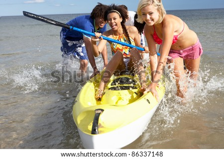 Teenagers in sea with canoe - stock photo