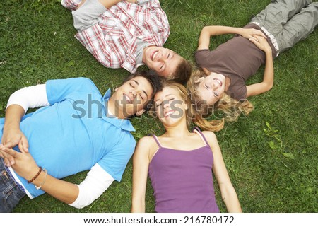 Teenagers lying down on the grass. - stock photo