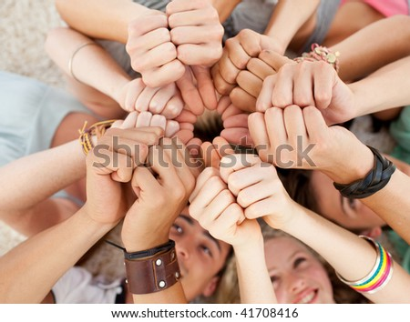 Teenagers lying on the floor with heads together and with thumbs up - stock photo