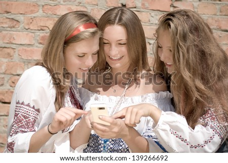 Teenagers Mobile World & three happy smiling teen girls in summer outdoors on the brick wall background - stock photo