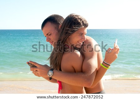 Teenagers on the beach with cellphones checking messages - stock photo