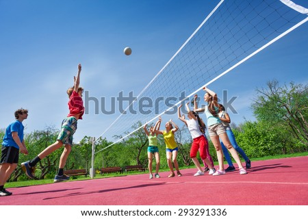 Teenagers play volleyball game on playing ground