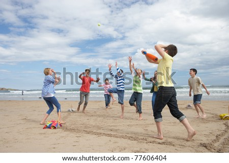 Teenagers playing baseball on beach