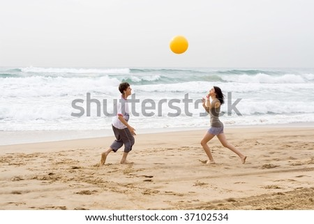 teenagers playing beach ball together