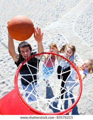 Teenagers playing outdoor basketball - stock photo