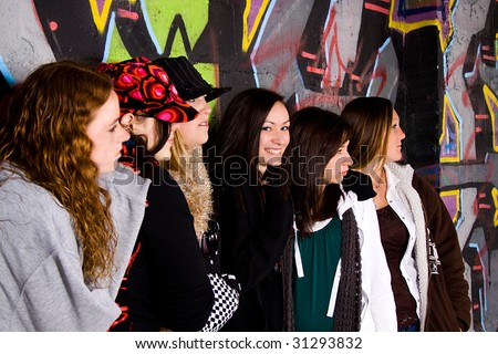 Teenagers Posing while One of them Looks at the Camera - stock photo