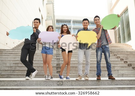 Teenagers posing with talk clouds on stairs - stock photo