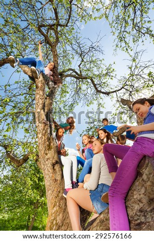 Teenagers sitting and holding mobiles on the tree - stock photo