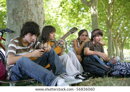 Teenagers sitting in the grass - stock photo