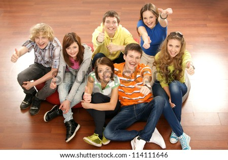 Teenagers sitting on the floor - stock photo