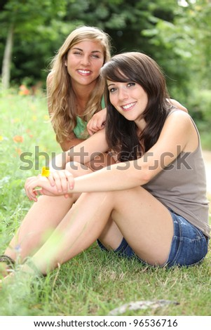 Teenagers sitting on the grass - stock photo