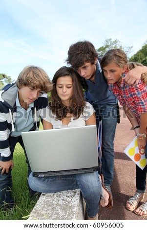 Teenagers sitting outside with laptop computer - stock photo