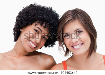 Teenagers smiling and posing against a colourless background - stock photo