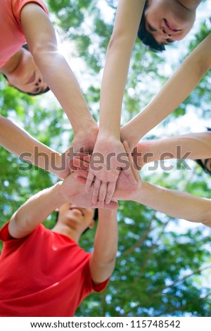 Teenagers stacking their hands - stock photo
